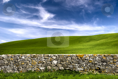 Stone wall stock photo, Beautiful green meadow with a old Stone wall by ikostudio