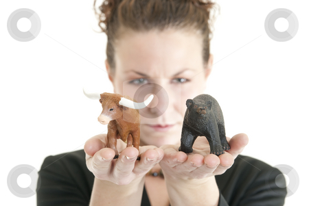 Uncertain market stock photo, Attractive Caucasian female holding a bull and bear symbolizing the stock market. Shallow DOF. Focus on bull and bear. by Christy Thompson