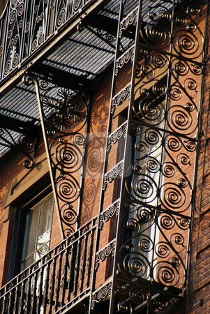Ornate fire escape stock photo, Ornate wrought iron fire escape attached to the outide of an old boston brownstone by Stephen Orsillo