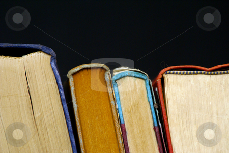 Four books stock photo, Old books lined up leaning on each other by Stephen Orsillo
