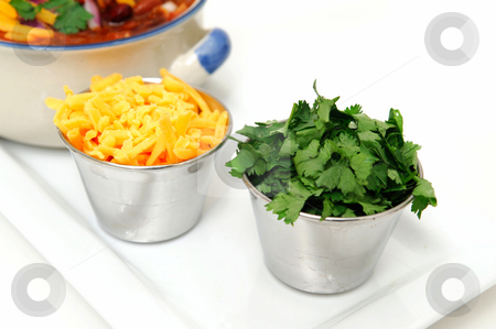 Chddar Cheese And Cilantro stock photo, Chili and beans in a ceramic bowl with onion, cilantro and cheddar cheese sprinkled on with with sides of each in stainless steel condiment cups. by Lynn Bendickson