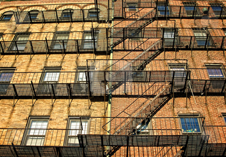 Wide escape stock photo, Fire escapes on old tenament buildings in boston massachusetts against a blue sky by Stephen Orsillo