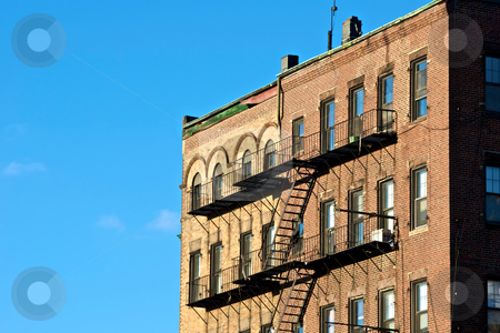 Escape stock photo, Fire escapes on old tenament buildings in boston massachusetts against a blue sky by Stephen Orsillo