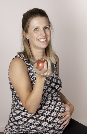 Pregnancy diet stock photo, Smiling pregnant woman eating a red apple by Jandrie Lombard