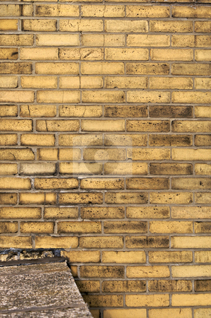 Yellow brick wall stock photo, Yellow brick wall background with ledge of cement connected to it by Stephen Orsillo
