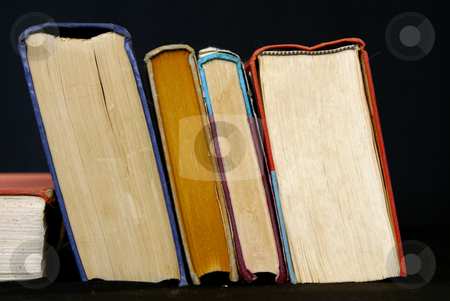 Leaning books stock photo, Stack of books leaning against black background by Stephen Orsillo