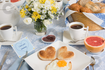 Eggs and hearts stock photo, Mother's day breakfast table with eggs and toast in heart shape by Anneke