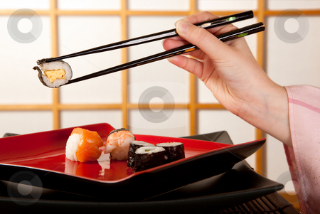 Chopsticks with sushi stock photo, Hands holding sushi with chopsticks in front of a japanese shoji sliding window by Anneke