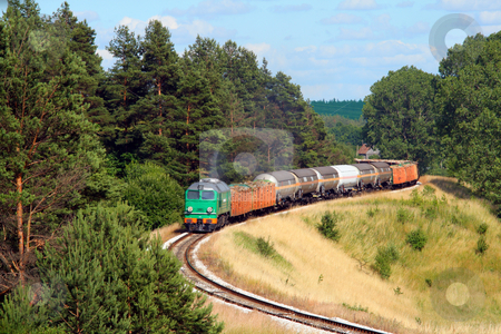 Freight train passing the forest stock photo, Freight train hauled by the diesel locomotive is passing its route by Jan Remisiewicz