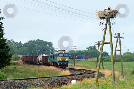 Rural landscape with freight train stock photo, Freight train passing through countryside with stork nest on the telegraph pole by Jan Remisiewicz