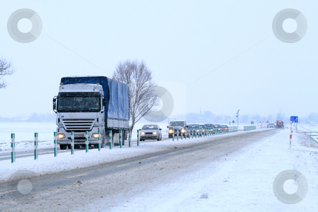 Winter scene on the road stock photo, Big rig passing through the snowy countryside by Jan Remisiewicz