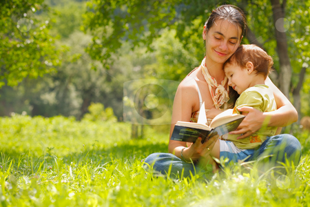 Happy mother and son reading a book outdoors stock photo, Happy mother and son reading a book outdoors by Roman Shyshak