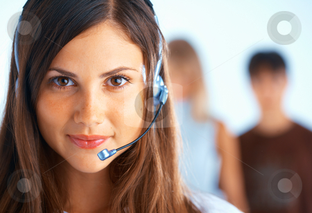 Call Center Operator stock photo, Young beautiful woman with headset with some people at the background by Roman Shyshak