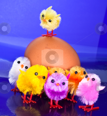 Chicks on top and in front of an egg stock photo, Toy orange and purple chicks in front of an egg by James Janisse