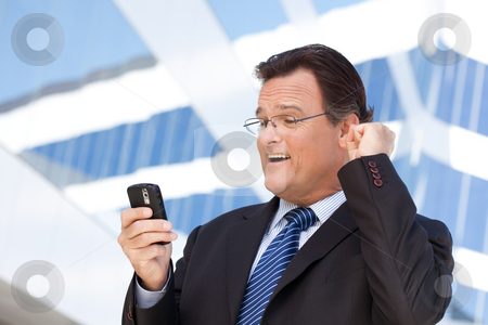 Businessman Looking at Cell Phone Clinches His Fist in Joy stock photo, Excited Businessman Looking at Cell Phone Clinches His Fist in Joy Outside of Corporate Building. by Andy Dean