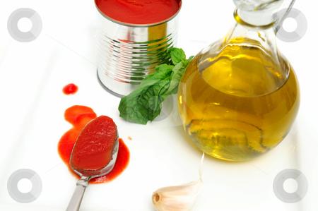 Marinara Sauce Ingredients stock photo, Marinara sauce ingredients including Olive oil, Basil leaves, fresh garlic and tomato sauce by Lynn Bendickson