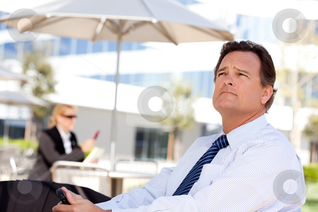 Handsome Businessman Looks Off Into the Distance stock photo, Handsome Businessman in Necktie Looks Off Into the Distance During a Break Outdoors. by Andy Dean