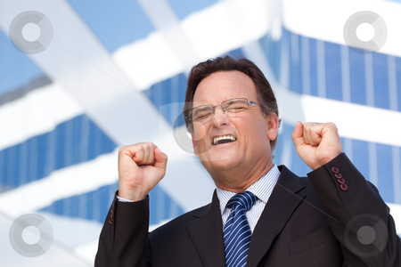 Happy Excited Businessman stock photo, Excited Businessman in Suit and Tie Clinches His Fists in Joy Outside of Corporate Building. by Andy Dean