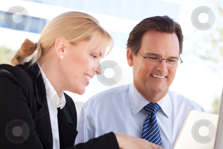 Businessman and Female Colleague Using Loptop Outdoors stock photo, Handsome Businessman Laughs While Working on the Laptop with Female Colleague Outdoors. by Andy Dean