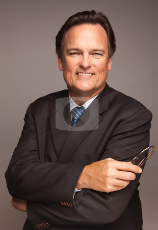 Handsome Businessman Portrait on White stock photo, Handsome Businessman Smiling in Suit and Tie Isolated on a Grey Background. by Andy Dean
