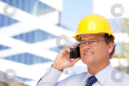 Contractor in Hardhat and Necktie Talks on His Cell Phone stock photo, Handsome Contractor in Hardhat and Necktie Smiles as He Talks on His Cell Phone. by Andy Dean