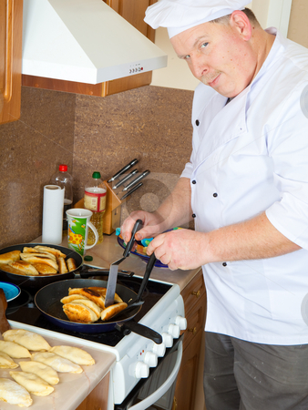Cook man in kitchen stock photo, Cook frying cakes on stove by Ruta Balciunaite