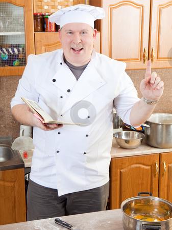 Cook man in kitchen stock photo, Cook reading recipe book by Ruta Balciunaite