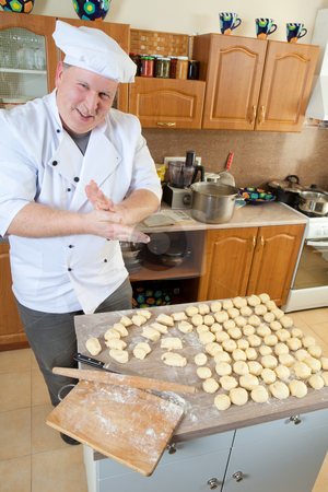 Cook man in kitchen stock photo, Cook rolling pastry pieces with hands by Ruta Balciunaite