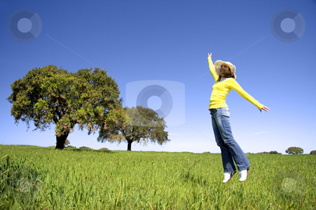 Happy Jump stock photo, Haapy woman jumping on a beautiful green meadow with trees by ikostudio