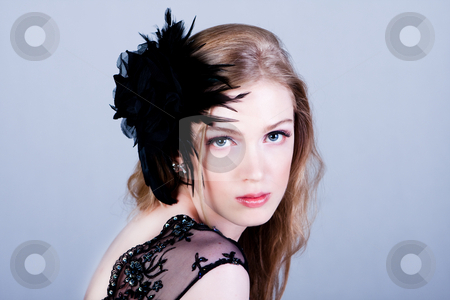 Attractive Young Woman Wearing Black stock photo, Attractive young woman wearing a black lace top and a black feather hairdressing. She is looking over her shoulder. Horizontal shot. by Angela Hawkey