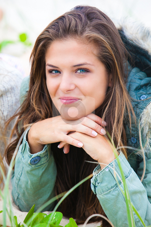 Smiling Young Woman Outdoors stock photo, Portrait of an attractive young woman wearing a coat and relaxing outdoors.  She is smiling at the camera and resting her chin on her hands. Vertical shot. by Angela Hawkey