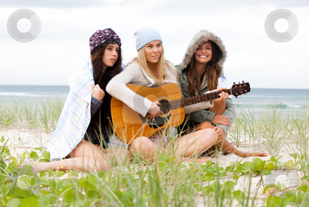 Young Women at the Beach With a Guitar stock photo, Three attractive young women sitting on the beach bundled up from the cold. One is playing a guitar. Horizontal shot. by Angela Hawkey
