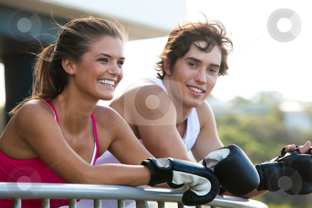 Young Couple in Boxing Gloves Leaning on Railing stock photo, Young couple leaning over a railing in an outdoor setting. They are both wearing boxing gloves and smiling. Horizontal shot. by Angela Hawkey