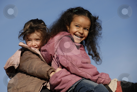 Two laughing girls stock photo, Two laughing little girls on a horse : the best friends by Bonzami Emmanuelle