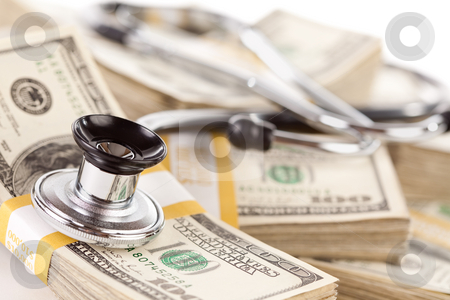 Stethoscope Laying on Stacks of Money stock photo, Stethoscope Laying on Stacks of Hundred Dollar Bills with Narrow Depth of Field. by Andy Dean