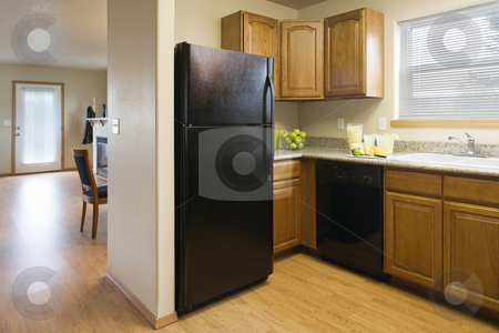 Kitchen in a Modest Home stock photo, View of a kitchen with a black refrigerator and wood cabinets, showing a partial view of the dining room and living room areas. Horizontal shot. by David Papazian