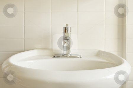 White Porcelain Sink and White Tile stock photo, Close-up of a modern stainless steel faucet on an oval, white porcelain pedestal-style sink against a white tile wall. Horizontal format. by David Papazian