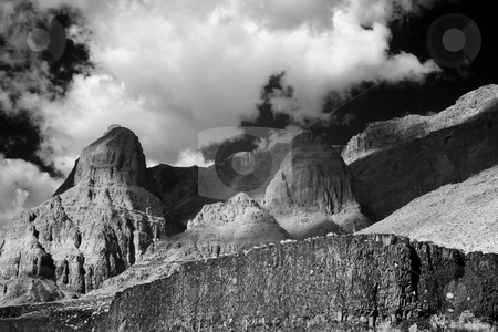Rock Formations and Puffy Clouds stock photo, Black-and-white low angle view of large desert rock formations, lava flows, and cliffs, with puffy clouds casting a shadow in Grand Canyon National Park. Horizontal shot. by David Marx