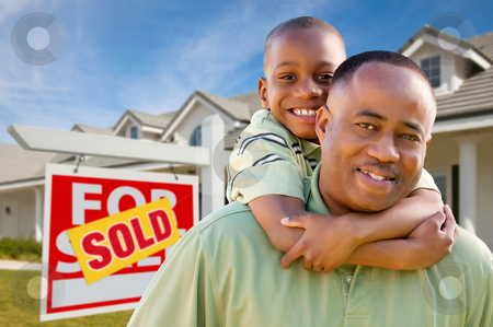 Father with Son In Front of Real Estate Sign and Home stock photo, Happy African American Father and Son in Front of New Home and Sold Real Estate Sign. by Andy Dean