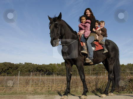 Riding family stock photo, Children and mother and a black stallion on a street by Bonzami Emmanuelle