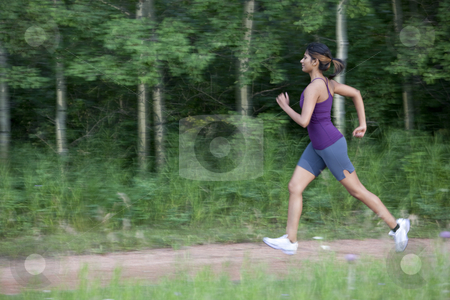 Attractive Young Female Power Walking stock photo, An attractive young woman in sportswear power walks on a park trail. Horizontal shot. by Dan Bannister