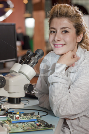 Attractive Young Female Researcher stock photo, An attractive young researcher sits at a desk with a microscope used to look at electronics. She is smiling towards the camera. Vertical shot. by Dan Bannister