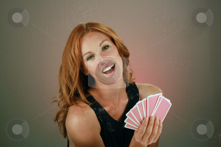 Beautiful Redhead with Playing Cards (6) stock photo, A lovely redhead model holds a hand of playing cards. by Carl Stewart