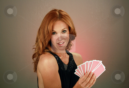 Beautiful Redhead with Playing Cards (7) stock photo, A lovely redhead model holds a hand of playing cards. by Carl Stewart