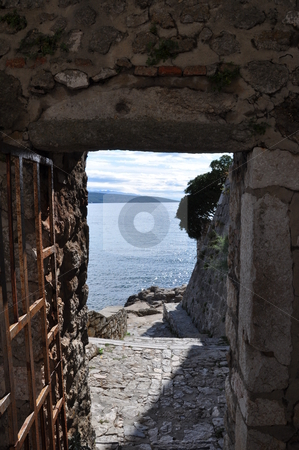 Ocean view stock photo, View through a passage in an old stone wall onto the ocean (Croatia) by Frank G?