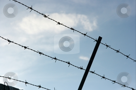 Fence stock photo, Barbed wire defense fence against blue sky by P?