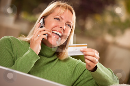 Cheerful Woman on Phone and Laptop with Credit Card stock photo, Cheerful Woman on Her Phone and Laptop with Credit Card. by Andy Dean