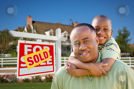 Father and Son In Front of Real Estate Sign and Home stock photo, Happy African American Father and Son in Front of New Home and Sold Real Estate Sign. by Andy Dean
