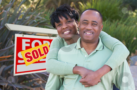 Happy Couple and Real Estate Sign stock photo, Happy African American Couple in Front of Sold Home For Sale Real Estate Sign. by Andy Dean