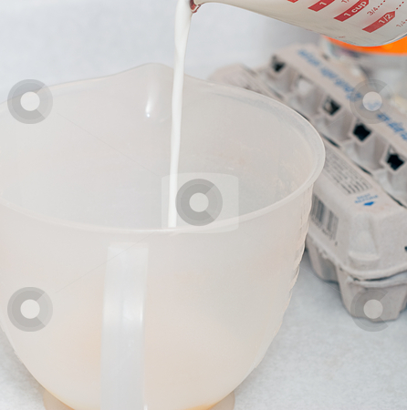 Measuring Milk stock photo, Milk is being measured in a plastic measuring cup by Richard Nelson